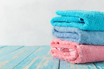 Stack of bath towels on wooden table with copy space