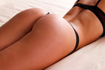 Sexy woman with beautiful buttocks laying on a bed
