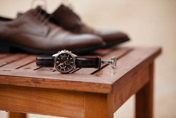 Expensive man wrist metal watch with leather strap and shoes on background