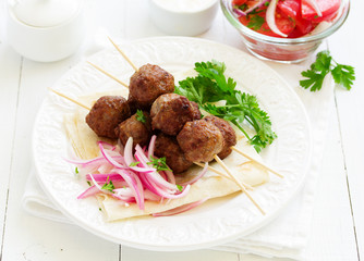 Lamb kebabs on skewers with onion and buttermilk sauce.