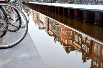Scenic view of bicycle and canal with the building reflection in the water, Amsterdam, Holland
