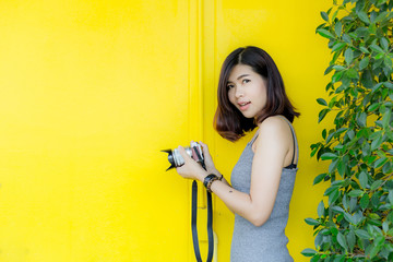 pretty young woman blowing red lips with camera over yellow background