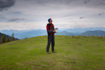 Man traveler, with remote controller of drone, stands on the alpine meadow