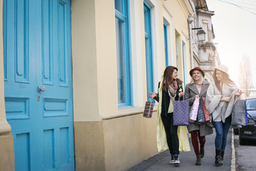 Three best friends walking on the street . Young female best friends doing shopping on the streets.