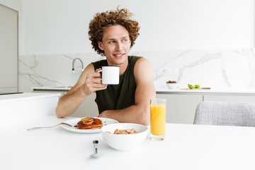 Handsome man sitting at the kitchen and drinking coffee
