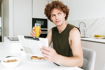 Handsome serious man holding newspaper and drinking juice