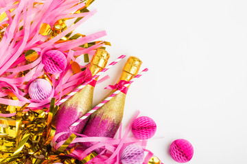 Pink and Gold Mini bottles of champagne with golden confetti and tinsel. Flat lay. New year celebration or wedding concept theme