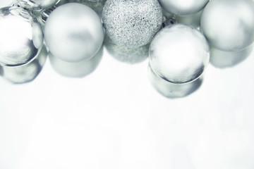 Silver Christmas balls on shiny background.