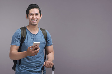 Handsome asian man using mobile phone while holding suitcase