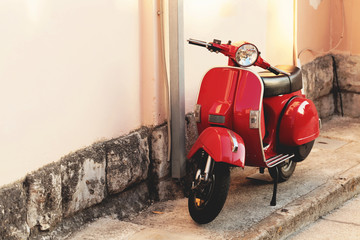 Photo sur Toile Scooter Red vintage scooter parked near a building wall - outdoors shot