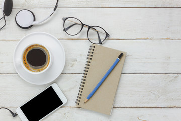 Top view / Flat Lay the pencil / note book / white mobile phone / listening radio music by headphones / black coffee and eyeglasses on rustic table wooden.An idea to relax time / rest or take a break.