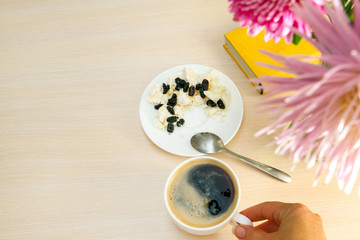 Drinking coffee from a white cup. Eating cottage cheese with blue raisins.