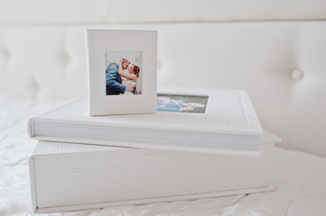 Elegant wedding photobooks or photo albums on the white bed background.