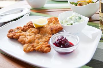 Schweineschnitzel Wiener Art mit Preiselbeeren, Gurkensalat und Bratkartoffeln im Restaurant