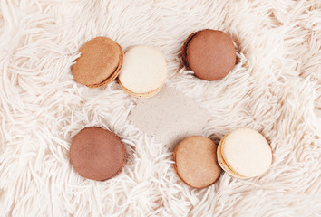Macarons with paper blank copy space. Macarons of coffee color on a soft background, with a blank for a design.