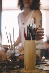 Artist girl paints picture on canvas in studio