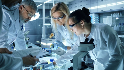 Team of Medical Research Scientists Work on a New Generation Disease Cure. They use Microscope, Test Tubes, Data Implementing Technology. Laboratory Looks Busy, Bright and Modern.