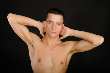 Male beauty. Athletic body. Young attractive guy. Black background.