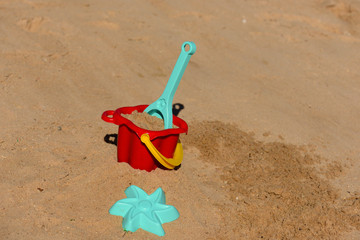 Baby beach toys - bucket, shovel and pask in the sand on a sunny day