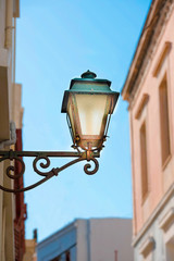 Street lamp of vintage design lighted on the wall in the afternoon.Syros island, Greece