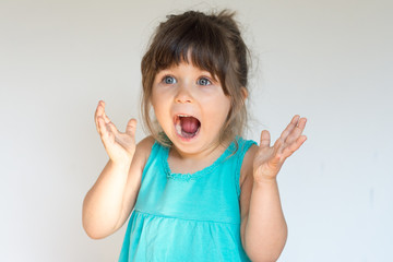 Surprised Cute child holding hands in surprised gesture, keeping mouth wide open, looking shocked