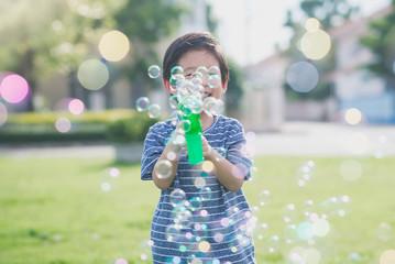 Asian child Shooting Bubbles from Bubble Gun