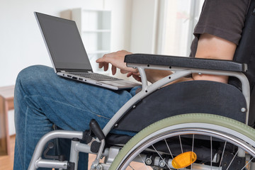 Handicapped disabled man on wheelchair is working with laptop in office.
