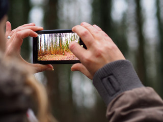 girl photographing forest