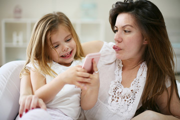 Smiling mother with daughter using smart phone on bed.