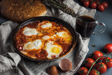 Shakshuka with pita bread in a pan. Fried eggs, onion, bell pepper, tomatoes and parsley on a rustic wooden table with ingredients.