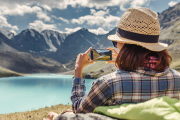 woman hiker taking photo of a mountain lake on her smartphone