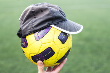 Soccer ball on a hand in a cap