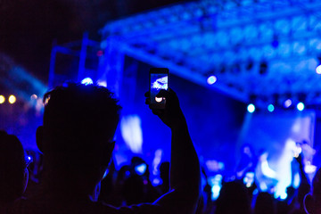 Hand with smartphone records live music festival, taking photo of concert stage live concert luxury party. Hand with smartphone records live music concert festival. Take photo in front of stage
