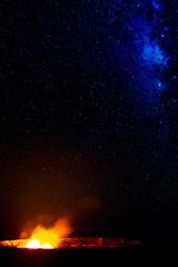 Ein Lavasee im  Halemaumau Krater auf dem Kilauea beleuchtet aufsteigende vulkanische Dämpfe vor der Milchstraße im Nachthimmel im Hawaii Volcanoes National Park auf Big Island, Hawaii, USA.