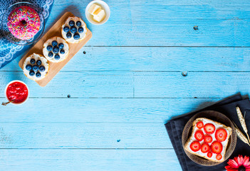 Delicious healthy breakfast, fruit sandwiches with different fillings, cheese, banana, strawberry, fishing, butter, blueberry, on a different wooden background.