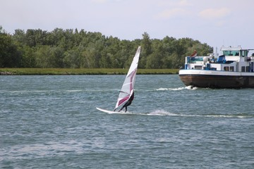 Windsurfer and transport ship sharing the river