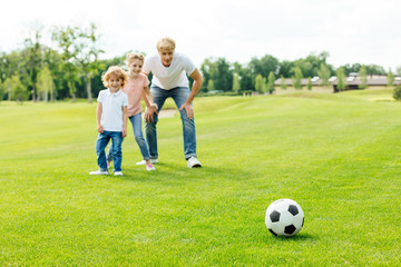happy father with daughter and son looking at soccer ball while standing on grass