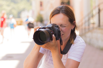 Young beautiful tourist woman taking photographs with digital photo camera. Wanderlust Concept