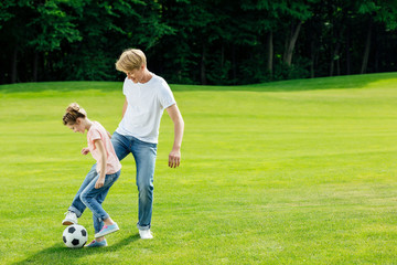 happy father and daughter playing soccer together on green lawn at park