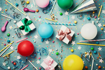 Birthday party background with colorful balloon, gift, confetti, cap, star, candy and streamer. Flat lay style. Festive greeting card.
