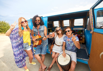 happy hippie friends playing music in minivan