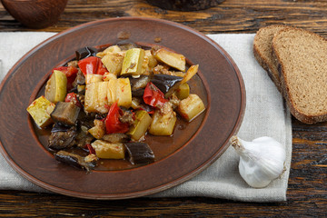 Vegetable stew with tomato, eggplant, zucchini, onion, carrot, pepper, close-up on a clay plate.