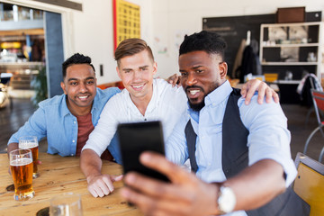 friends taking selfie and drinking beer at bar