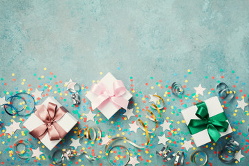 Gift or present box decorated colorful confetti, star and streamer on blue vintage table top view. Flat lay style. Birthday background. Festive border with copy space.