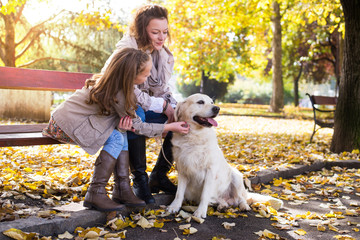 Family woman and her daughter walk autumn park,with his dog golden retriever
