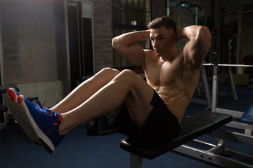 young man doing sit-up abdominal exercises in gym