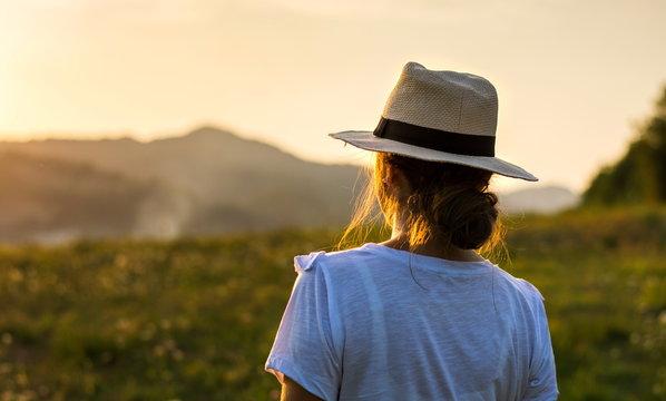 Girl enjoying sunset over a hill