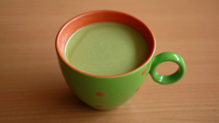 Secangkir teh hijau matcha latte dengan latar belakang kayu.