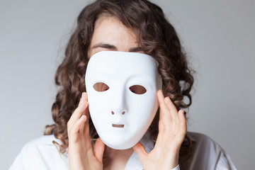 woman putting a white mask on her face