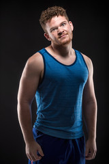 Attractive and muscular athlete studio shot of young handsome sportsman on black background.